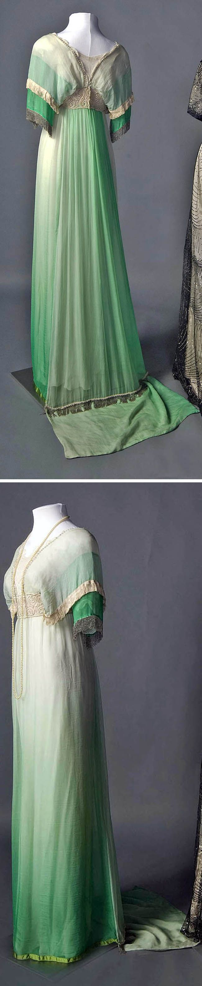 """Evening dress, probably French, ca. 1911-13. Smith College Historic Clothing: """"The Empire style of a straight column of drapery and a high waist was high fashion especially in the years 1912 and 1913. Heavy fringe on delicate fabrics was popular, too, like the white silk fringe and silver beaded fringe on the sleeves and on the train of the green dress. The bodice is trimmed with pale pink pearls and pink chiffon rose buds."""""""
