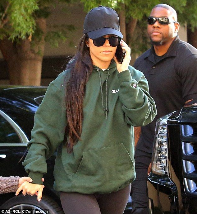 Casual look: The 37-year-old wore a green sweater and a black hat on her day out...
