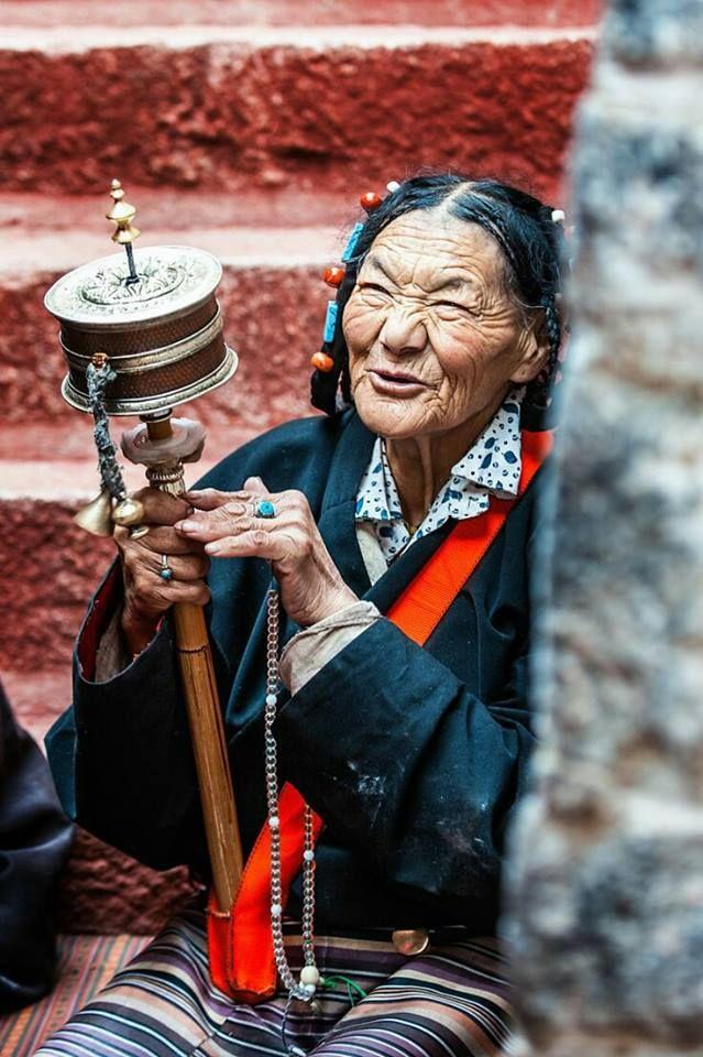 Tibeterin mit trad. Schmuck und Gebetsmühle