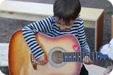 A cute child learning how to play a guitar during our summer camp this year 2013.