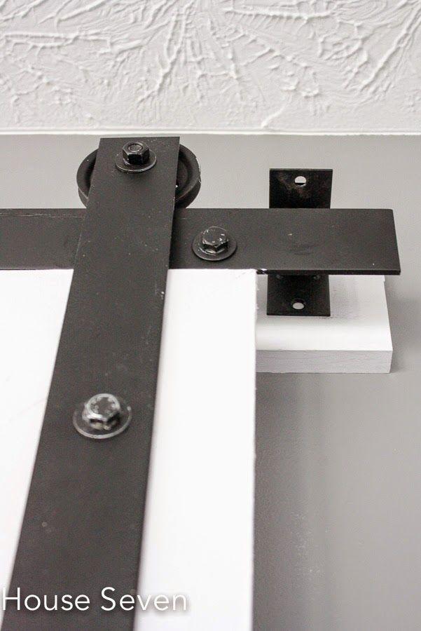 Barn Door Tutorial | DIY Barn Door Hardware | AWESOME use of garage door pulleys (cheap) and metal - just have to find long piece - would make door differently