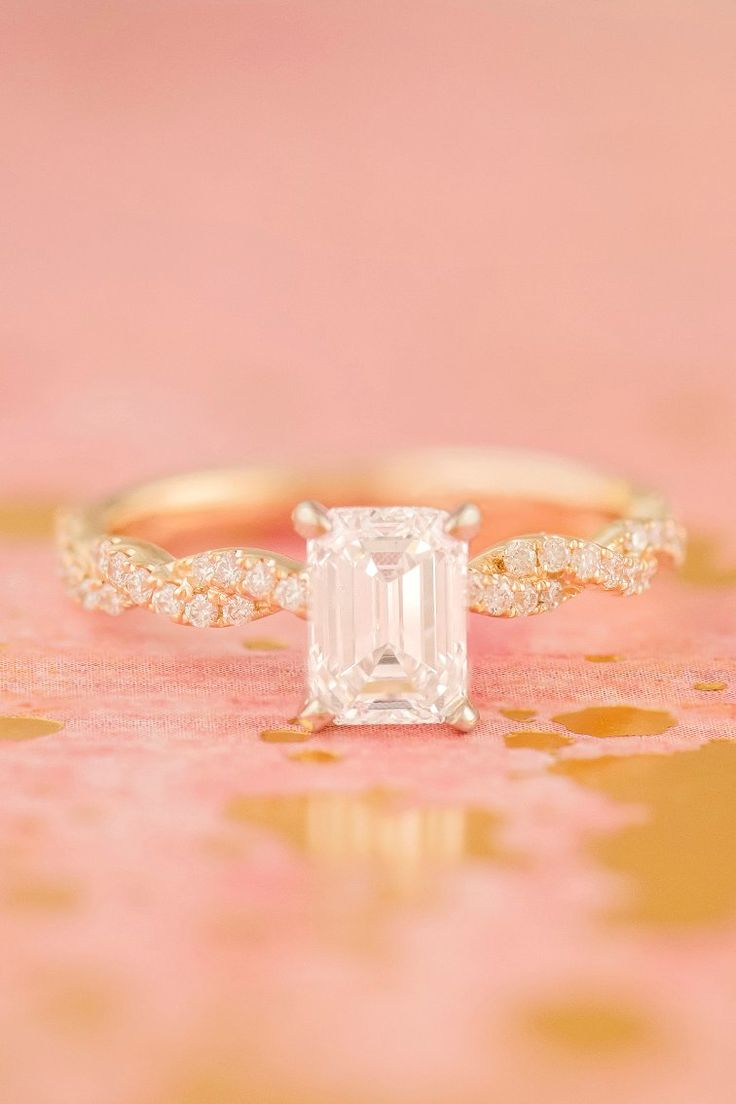 A charming infinity diamond engagement ring with a pavé setting in classic 14k yellow gold. A unique one-carat emerald cut diamond center stone is accented by 36 sparkling round diamonds along the band.
