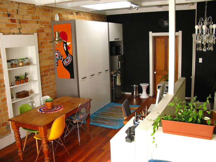 Exposed brick, contrasting black wall, colorful room accessories. Love it.