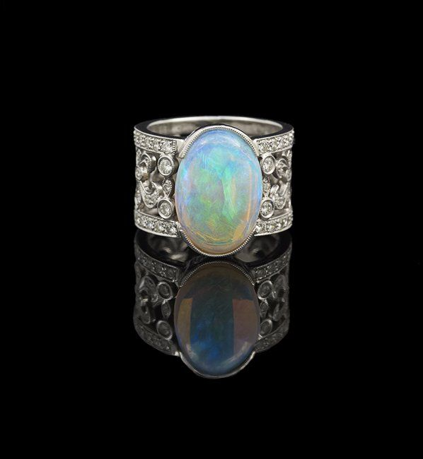 Eighteen-Karat White Gold, Opal and Diamond Ring, with a wide band and set with a blue-green-colored crystal opal, with an approximate weight of 4.88 carats, and the ring band set with sixty-four round brilliant-cut diamonds, with an approximate total weight of 0.84 carats, approximate color E-G and clarity VVS2-VS1, size 7-1/2, 10.0 grams total weight.