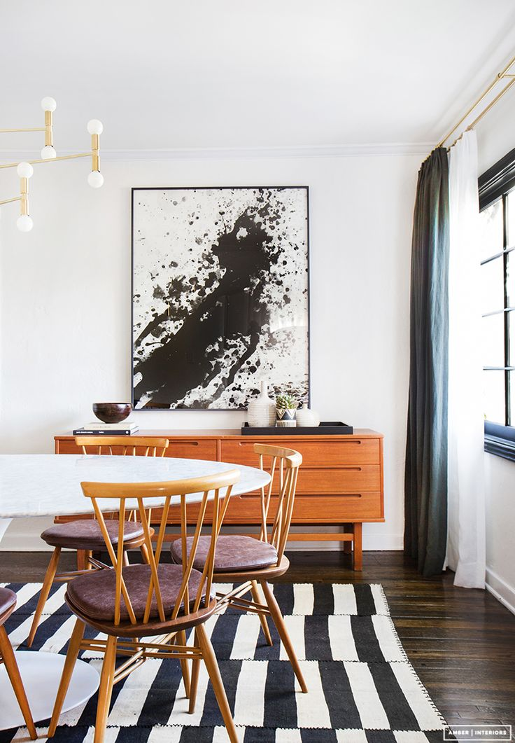 Midcentury modern dining room with a buffet with large art and a stripped rug