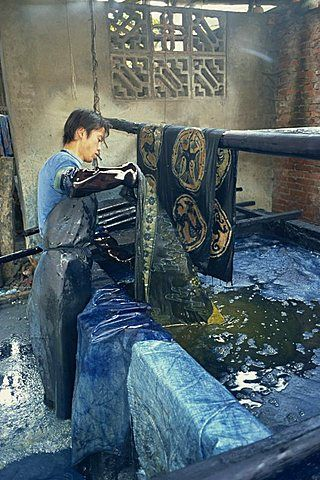 Dipping batik in an indigo vat, Guizhou, China, Asia