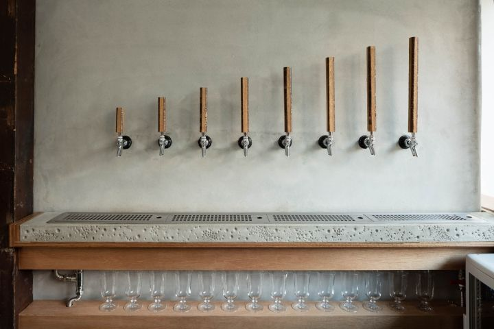 The originality of the beer tap handles is achieved by slicing off four sides of a cherry blossom branch to create an octagonal shape. The irregularity in length and color of the wooden handles adds to the unique character of the bar.