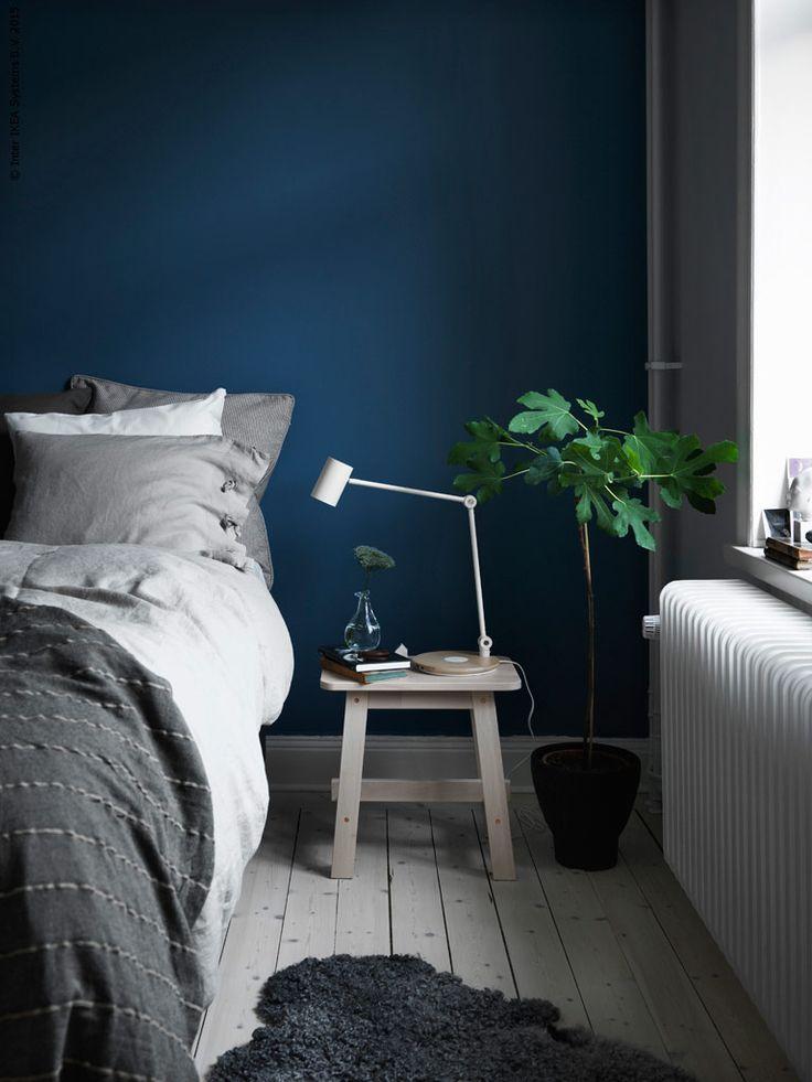 En rofylld och nattblå vägg i sovrummet lyfter fram den sköna materialkänslan i trärena pallen NORRÅKER och LINBLOMMA lakan i linne. RIGGAD arbetslampa med trådlös laddning, SINNERLIG kruka, VÅRVIND vas, TALLÖRT överkast, SINNERLIG kuddfodral.