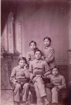 "(I do believe my great grandfather had a similar experience) Native children were taken from their homes and shipped over vast distances to boarding schools, required of all Native children between the ages of 10-18. Children were shorn of their identities in every way, including name, style of dress, and even personal appearance... Students were... taught that they were inferior, and that the school was there to ""raise them up"" from savagery to the level of non-Natives."