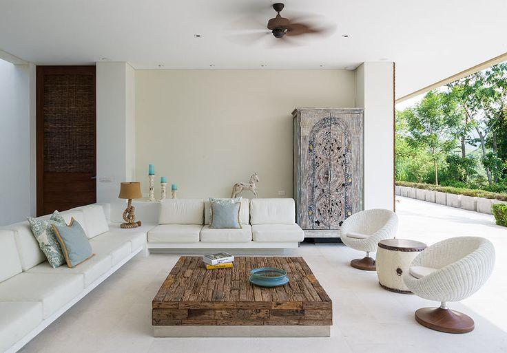 """La sala está amueblada por piezas temáticas como el mueble bar, construido a partir de una puerta africana. La mesa de centro es de Artefacto, las sillas blancas brasileras son de Saccaro y el sofá en """"L"""" está hecho en mampostería."""