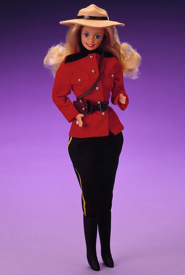 Hello and Bonjour from Canada, your neighbor to the north! Canadian Barbie doll is dressed in a typical Canadian Mountie uniform. Her red jacket is inspired by Canada's national symbol — the red maple leaf. Her black puffy pants are accented with golden trim, and tucked into black boots. She wears a wide-brimmed Mountie hat, under which her long blond hair falls over her shoulders.
