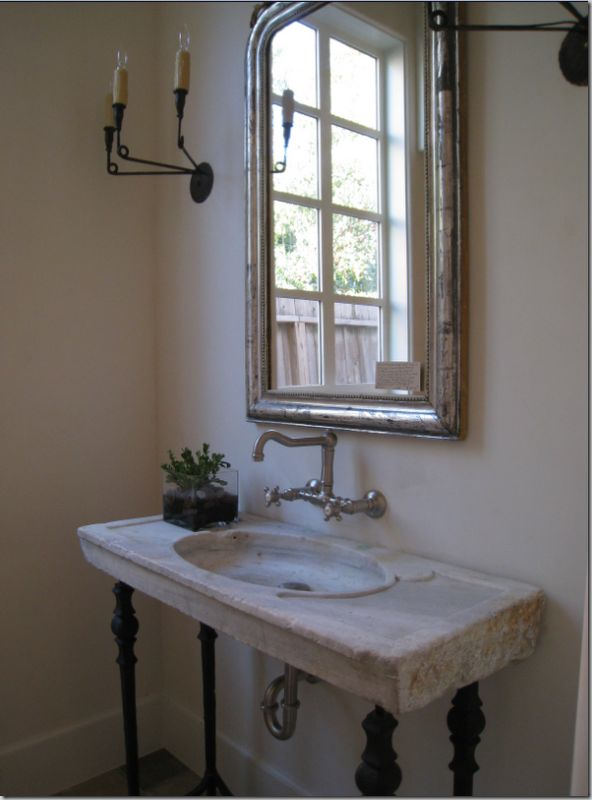 The powder room has an antique sink on iron legs with wall hung fixtures. Simple three armed black iron sconces flank the silver leafed Louis Phillipe mirror.