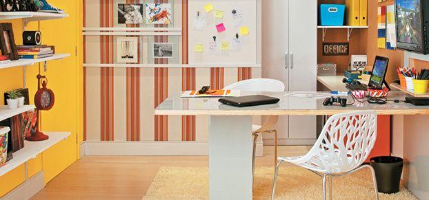 O quarto reúne funções de home office e canto de lazer na casa. A bancada acolhe duas pessoas e seus computadores, e ainda há espaço para a TV, livros e materiais