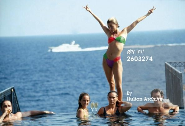 Marie Chantal Miller, future wife of Prince Pavlos of Greece, strikes an extravagant pose above her sister Pia (in yellow), who is soon to marry Christopher Getty. They are lounging in the pool of the Hotel Belair, Cap Ferrat, July 1991. (Photo by Slim Aarons/Hulton Archive/Getty Images)