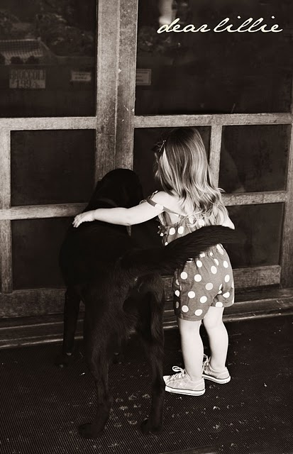 I'm pretty sure that puppy in hugging the little girl with it's tail. Seriously adorable!