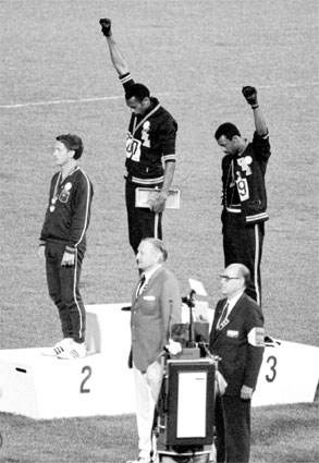Medalists Tommie Smith and Juan Carlos raise black power salute during the US national anthem.