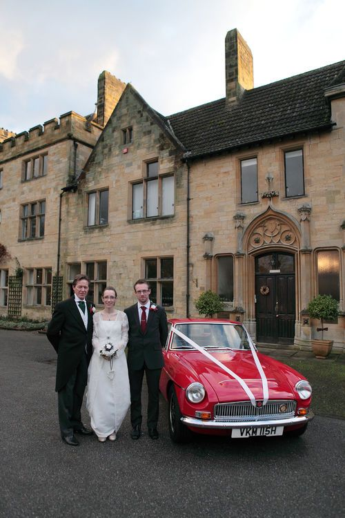 Bride and groom with a traditional British sports car