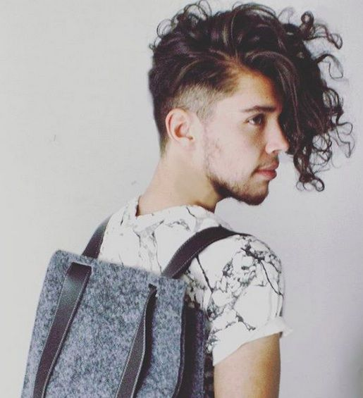 A photograph of a curly guy with a long undercut hairstyle