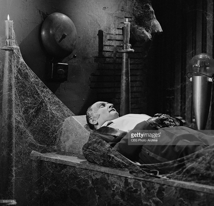 American actor (and later political activist) Al Lewis in the role of 'Grandpa' wears evening dress as he sleeps in a cobwebbed room beneath a large alarm bell in a still from the CBS television situation comedy 'The Munsters' episode 'Just Another Pretty Face,' November 12, 1965.