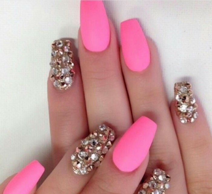 eight nails, four of which are painted hot pink, the other fore visible are entirely covered with rhinestones