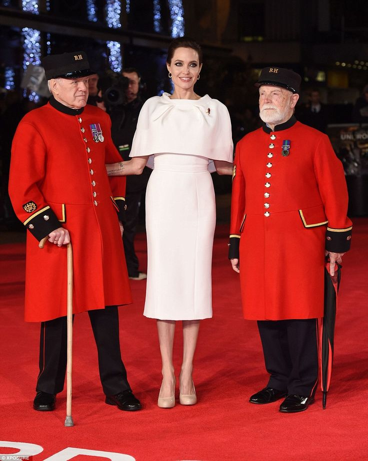 Moving movie moment: Angelina proudly poses with two Chelsea Pensioners in their garb as the festivies