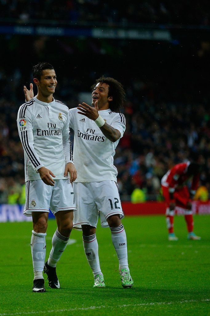Cristiano Ronaldo (L) of Real Madrid CF celebrates scoring their fifth goal with teammate Marcelo (R) during the La Liga match between Real Madrid CF and Rayo Vallecano de Madrid at Estadio Santiago Bernabeu on November 8, 2014 in Madrid, Spain.