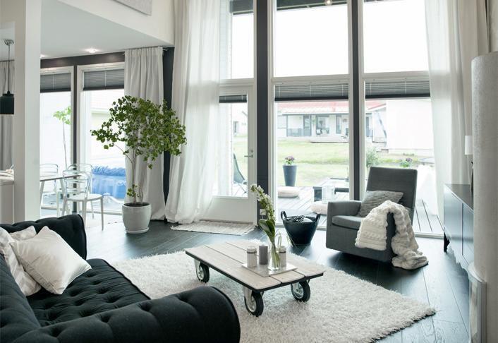 Olohuoneeseen ei ole sijoitettu liikaa kalusteita, jotta korkean tilan avara vaikutelma säilyy. Musta sohva on hollantilaisen Eichholtzin mallistosta. | Itse tehty unelmatalo | Koti ja keittiö | Tanja Hakala | Kuva Eveliina Mustonen