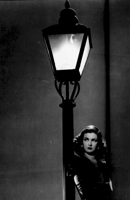 The women are mad narrative perpetuated by film noir. A lamp, a light and a person.  Just enough light is thrown across the top of the actress and a little hint of light on the arms.