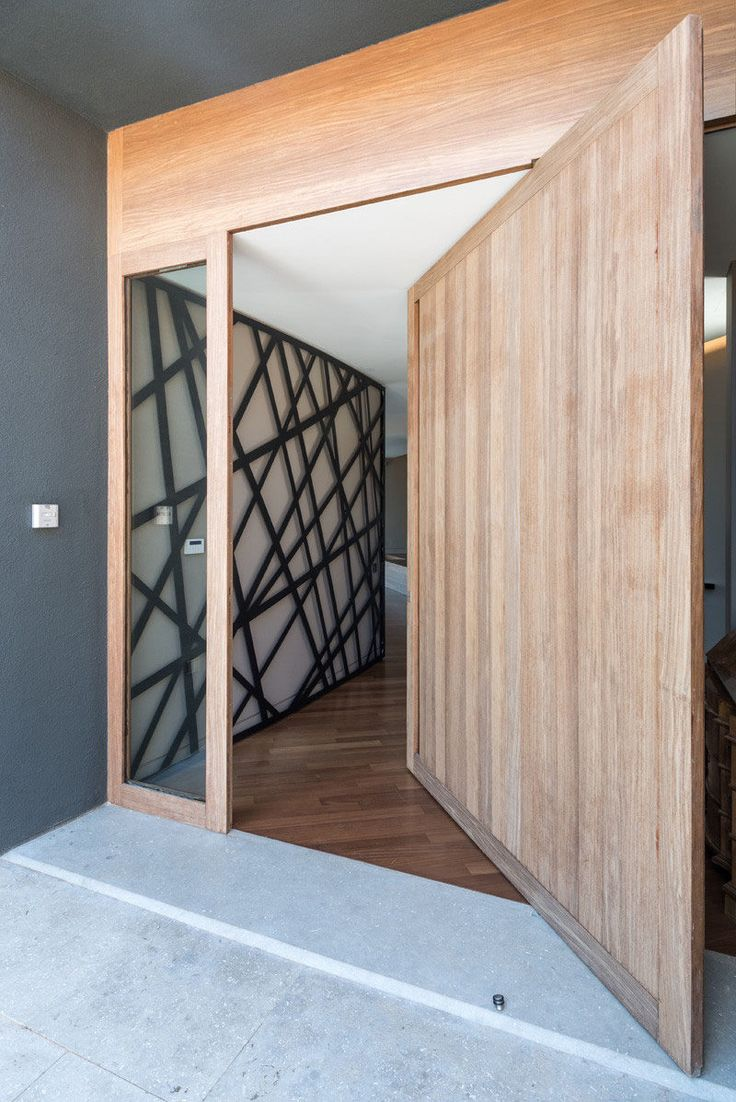 A large light wood pivoting door greets people at the front of this modern Greek home.