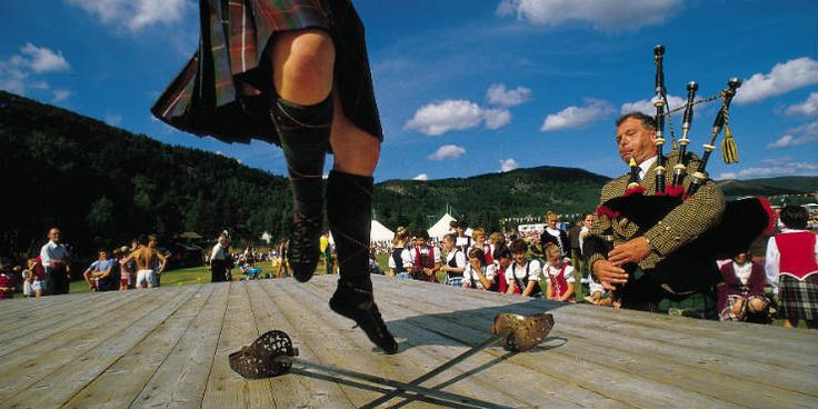 A Highland dancer taking part in the sword dancing event whilst a piper plays at the Ballater Highland Games