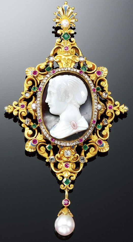 GOLD, HARD STONE ENAMEL AND GEM-SET PENDANT, CIRCA 1880. In the Renaissance Revival style, the agate cameo of a female profile to the left within a rose-cut diamond and ruby border, the open work gold scroll frame set with step-cut and cushion-shaped rubies, emeralds and diamonds and highlighted with blue and white enamel, embellished by a gargoyle surmounting the cameo and supporting a detachable pearl drop, the reverse engraved with foliate motifs, provided with a pin fitting.