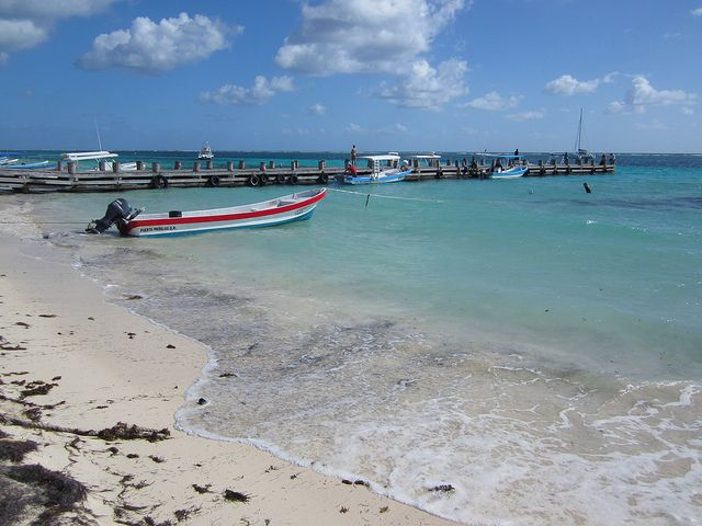 A wooden dock in Puerto Morelos stretches into the water from a white beach dotted with clumps of sea grasses.