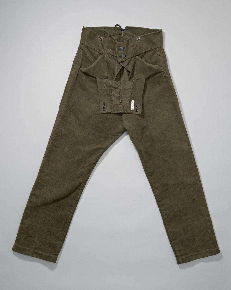 Olijfkleurige bevertien klepbroek gedragen door ongehuwde jongemannen, als pronkkleding bij de zondagse kerkdracht. De reguliere zondagse broek was zwart van kleur | Nederlands Openluchtmuseum | ca. 1920-1956