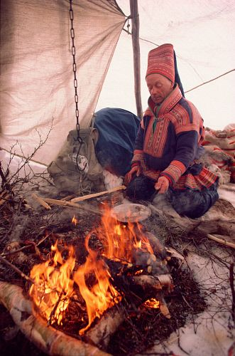 Sami reindeer herder, Aslak, cooks over a fire in his tent on spring migration. North Norway.: Kautokeino, Norwegian Lapland.