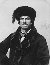 Mixed-blood fur trader, c. 1870. Black and white photograph of a man with a short moustache and earrings, wearing a fur lined dress jacket, bow tie and fur hat