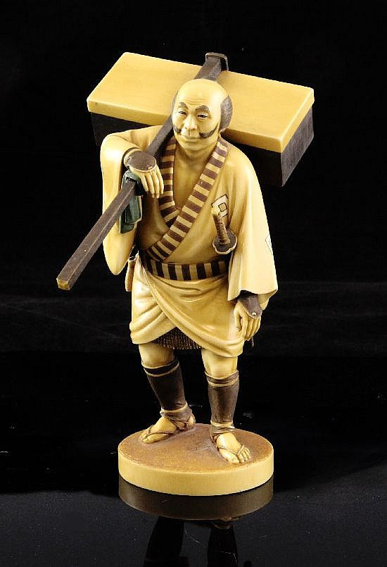 A fine Japanese ivory stained okimono of a travelling man, Taisho period, carrying a case upon his back, a sword strapped to his waist, on an oval base, two character signature to a red lacquer tablet, 7.3in.