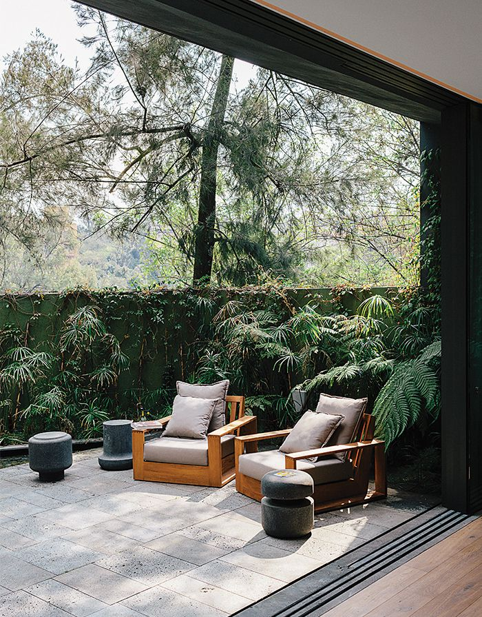 Recinto lava stone lines a patio adjacent to the living room in designer Ezequiel Farca's house in Mexico City. He designed the #teak outdoor furniture, including two arm-chairs.