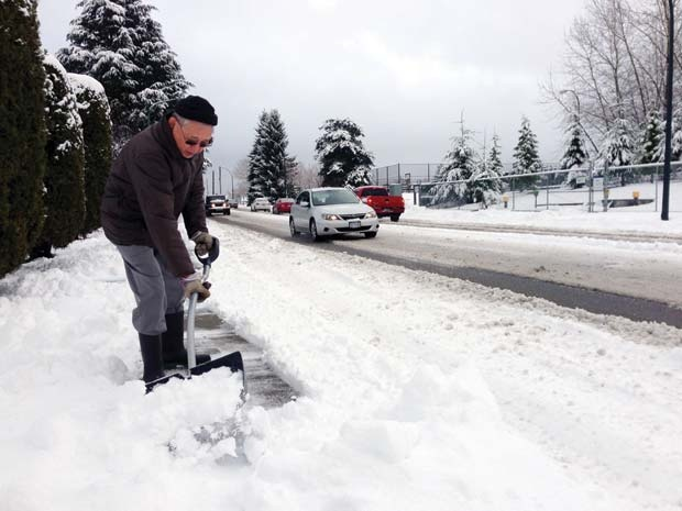 Slippery conditions: Yuji Kado spent Monday morning shovelling snow from the sidewalk on 10th Avenue and Coquitlam Street in Burnaby. The city had more than a dozen snow trucks plowing and salting the streets Tuesday morning.