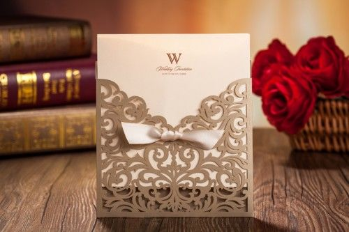 This Gold pocket invitation features a beautiful traditional laser cut pattern evocative of a classic wedding style. The pattern is complemented by a luxurious ribbon. The invite is ideal for couples