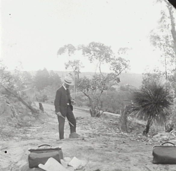 Title: The old and new roads, Linden Date & Location: December 1905, 	 Blue Mountains (NSW); Linden (NSW) Description: Black and white glass lantern slide. Title in ink on upper edge label. Notes 	 Botanist and public servant Joseph Maiden inspecting remnants of old Western Road near Linden, with new road and railway in the background. Foreground shows two medical style bags with unfolded charts. From negative in Mitchell Library Frank Walker Collection ON 150, Item 95.
