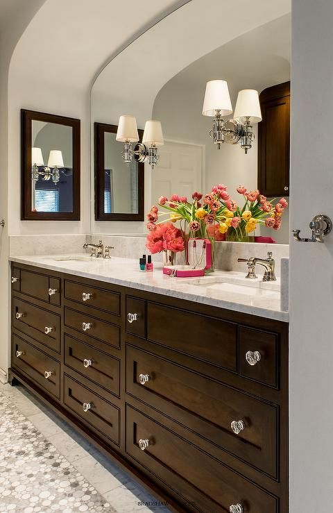 Chic bathroom boasts an arched alcove filled with a dark brown double washstand adorned with glass knobs topped with white marble fitted with his and hers sinks under an arched mirror lit by Thomas O'Brien Jonathan Sconces flanked by dark brown medicine cabinets.