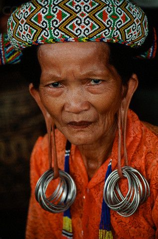 **Indonesia ~Borneo | A Dayak woman wears heavy earrings which pull down on her earlobes in a village near Mahakan River |  © Charles & Josette Lenars