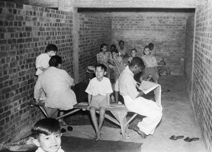 The Japanese Campaign and Victory 8 December 1941 - 15 February 1942: Civilians in a Singapore air raid shelter during a Japanese bombing raid.