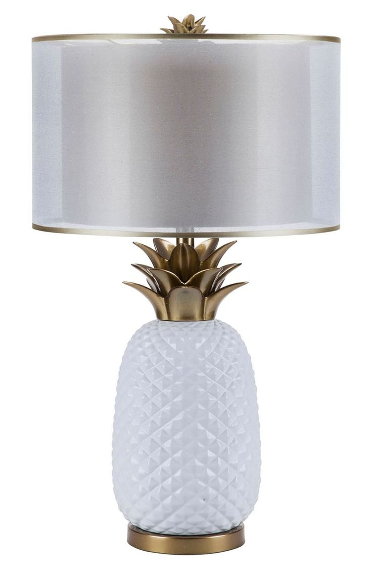 Add a welcoming, tropical touch to the interior décor with this glossy ceramic lamp fashioned in the shape of a pineapple, complete with polished brasstone leaves and a double-layered shade.