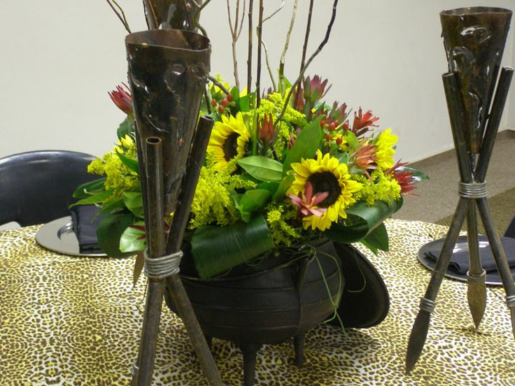 African pot with sunflowers and assegai stands as the centerpiece on a Zulu themed table