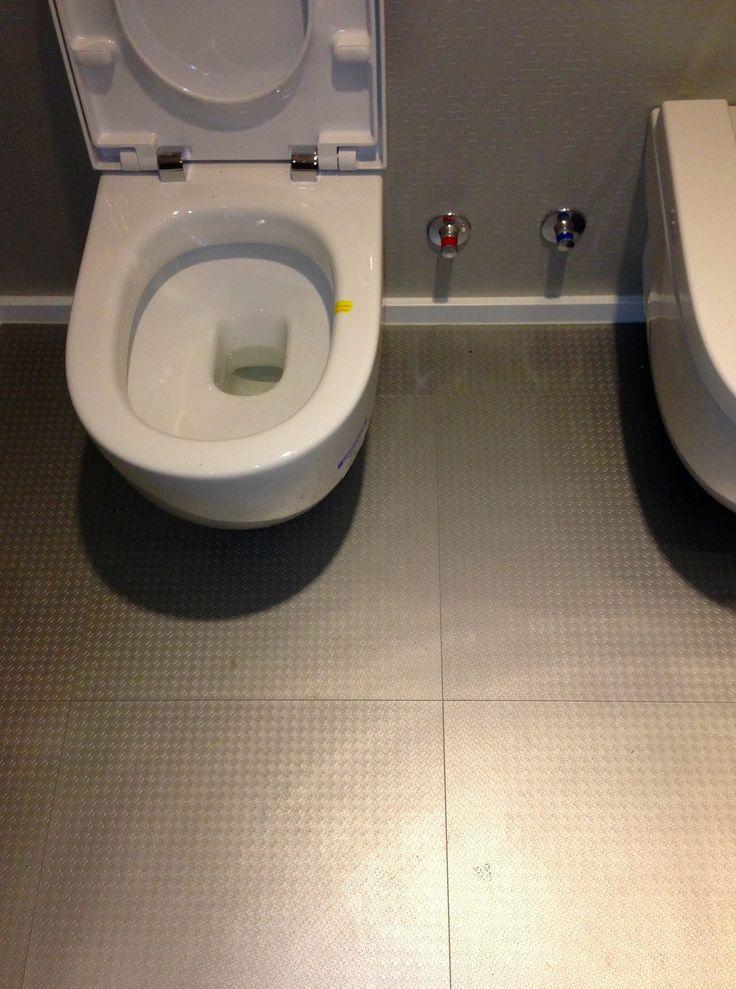 Baño con losetas vinilicas de tarkett y paredes de revestimiento mural vescom