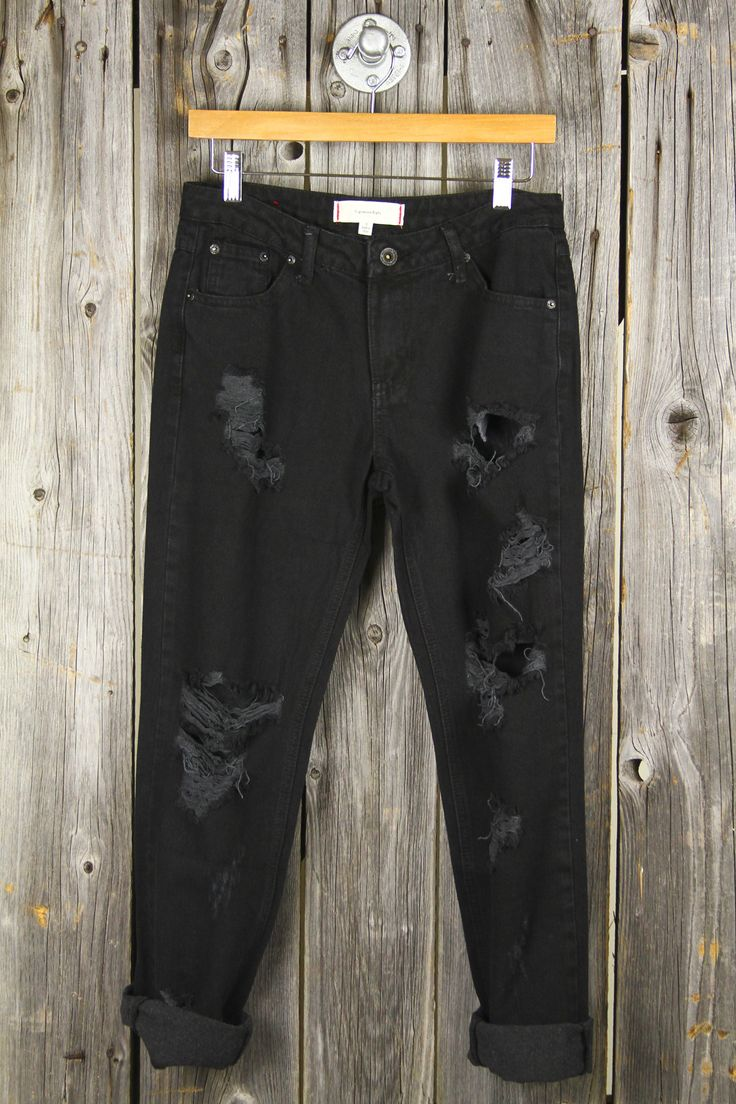 """Our black rinse boyfriend jeans feature destructed tears and a zip-up fly. · Loose Fit Design + High Waist · 29"""" Inseam, 9"""" Rise · Both Legs Feature Horizontal Rips + Holes"""