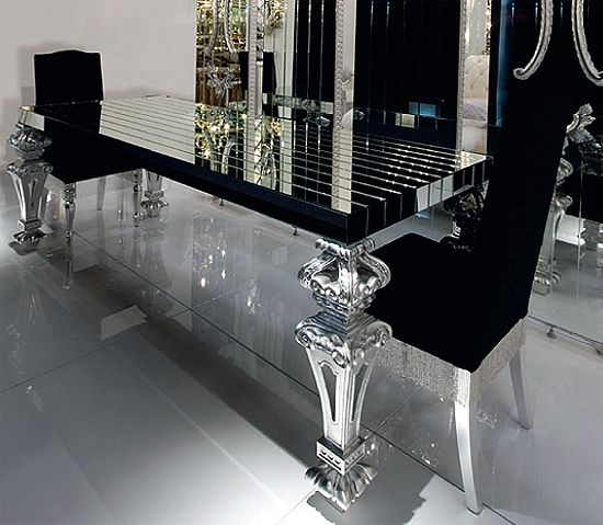 A luxury designer glass table with architectural top in reeded black glass mirror emphasising the bold, crisp and pure silhouette contrasting with the 18th C classically referenced prominent legs finished in silver leaf.
