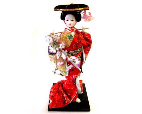 This beautiful ceramic Japanese Geisha doll features a Geisha dressed in a a traditional red and gold kimono, accented with metallic gold.