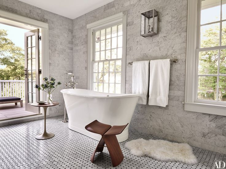 In the East Hampton, New York, home of publishing-world powerhouses Pilar Guzmán and Chris Mitchell, the Carrara-marble-lined master bath is accented with a vintage Sori Yanagi stool.